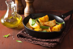 Baked potato wedges in black frying pan Royalty Free Stock Photography