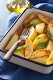 Baked potato wedges in enamel baking dish Royalty Free Stock Photos
