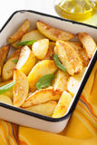 Baked potato wedges in enamel baking dish Stock Images