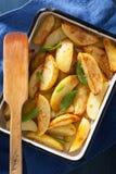 Baked potato wedges in enamel baking dish Royalty Free Stock Image