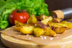 Baked potato wedges with fresh tomato and green salad Stock Photo