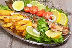 Baked potato wedges and grilled fish Stock Image