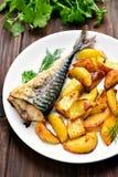 Baked potato wedges and mackerel fish Royalty Free Stock Photo