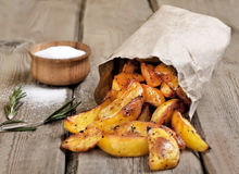 Baked potato wedges in paper bag Stock Images