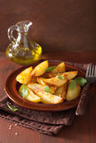 Baked potato wedges in plate over brown rustic table Royalty Free Stock Photo