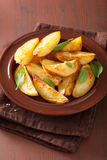 Baked potato wedges in plate over brown rustic table Stock Photo