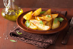 Baked potato wedges in plate over brown rustic table Stock Image