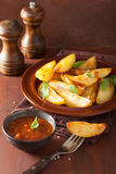 Baked potato wedges in plate over brown rustic table Royalty Free Stock Image