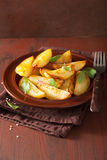 Baked potato wedges in plate over brown rustic table Royalty Free Stock Photography