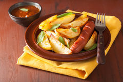 Baked potato wedges in plate over brown rustic table Stock Photography