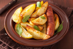 Baked potato wedges and sausage in plate over brown rustic table Stock Photo