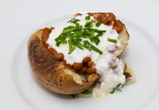 Baked Potatoe with Beans, Cottage Cheese and Chives. Closeup to a baked potatoe with baked beans, cottage cheese and chives on it Stock Images