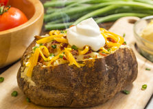 Baked potatoe supreme. Fresh hot baked potato with butter bacon cheese and chives topped with sour cream on a cutting board royalty free stock image