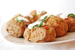 Baked potatoes. Stuffed with red kidney and black olives, served with white cream and rosemary Stock Photos