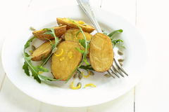Baked potatoes with arugula and lemon zest Stock Images