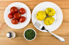 Baked potatoes with dill, bowl with greens, salt, pickled tomato Stock Photo