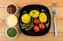 Baked potatoes with dill, pickled gherkins and tomatoes, greens, Stock Photography