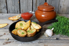 Baked potatoes with dill in village in a cast iron frying pan Royalty Free Stock Photos