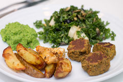 Baked potatoes, falafels, pea mousse and salad on white plate. Baked potatoes, falafels, pea mousse and kale pear blueberry pumpkin sees salad on white plate Stock Photo