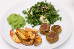 Baked potatoes, falafels, pea mousse and salad on white plate. Baked potatoes, falafels, pea mousse and kale pear blueberry pumpkin sees salad on white plate Royalty Free Stock Photography