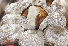 Baked potatoes in foil at a buffet Royalty Free Stock Photography