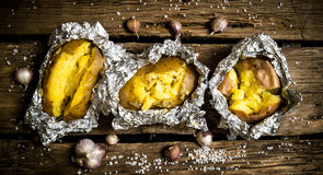 Baked potatoes in foil on a wooden table . Royalty Free Stock Photography