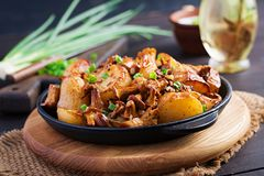 Baked potatoes with garlic, herbs and fried chanterelles. In a cast iron skillet stock photos