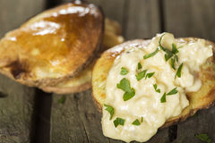 Baked potatoes with garlic sauce. Close up of some Baked potatoes with garlic sauce over rustic wooden background Stock Photo