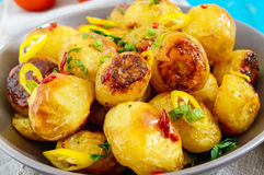 Baked potatoes with a golden crust with hot pepper, garlic, spices and herbs in bowl. Close-up royalty free stock image
