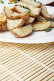 Baked potatoes with green onions on a white plate. Organic Vegetarian Food on a bamboo mat Stock Image