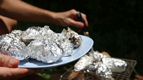 Baked potatoes on the grill in foil at the stake stock video footage