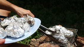 Baked potatoes on the grill in foil at the stake stock video