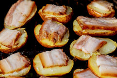 Baked potatoes grilled on skewers. Street festival food. Royalty Free Stock Photo
