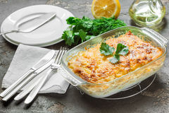 Baked potatoes with melted cheese, fresh green apple and lemon. Potato gratin with cream cheese and fresh herbs Stock Photo