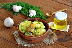 Baked potatoes with mushrooms and spices. Delicious rustic lunch, dinner. Green dill, fresh mushrooms, sunflower oil, spoon Stock Photography