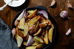 Baked potatoes with onion and garlic Stock Image