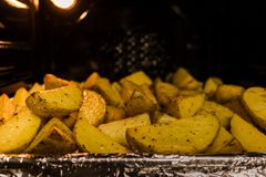 Baked potatoes in the oven on a kitchen tray royalty free stock photos