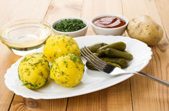 Baked potatoes with pickled cucumbers, greens, ketchup in bowl, Stock Photo