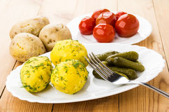 Baked potatoes with pickled gherkins on dish, marinated tomatoes Stock Photo