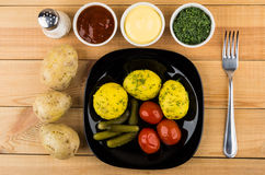 Baked potatoes, pickled gherkins and tomatoes, greens, bowls wit Royalty Free Stock Images