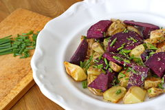 Baked potatoes with raw beetroot and chive Stock Photography