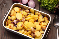 Baked potatoes in a roasting pan with garlic and onion Stock Image