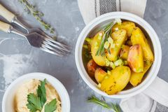 Baked potatoes with rosemary and green onions in white ceramic f Stock Image
