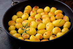 Baked potatoes with rosemary and pepper. In a frying pan on black background Stock Images