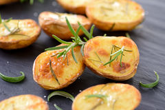 Baked potatoes. Baked and salted potatoes with rosemary on a slate Royalty Free Stock Photos