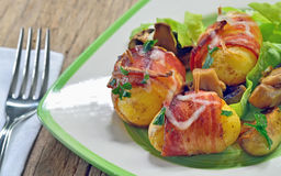 Baked potatoes wrapped in bacon Stock Photos