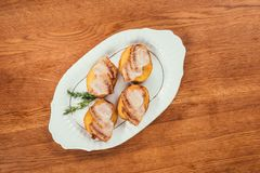 Baked potatos with ham slices. On top laying on plate over wooden surface Stock Photography