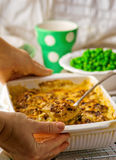 Baked pudding with fish and mushrooms in a ceramic form for roasting and green peas in a bowl. Stock Images