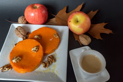 Baked pumpkin with addition of Honey and walnuts, autumn leafs and cup of coffee Stock Photos