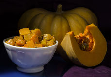 Baked pumpkin. Ceramic bowl with baked pumpkin with spices, piece of pumpkin and sunflower seeds Stock Image
